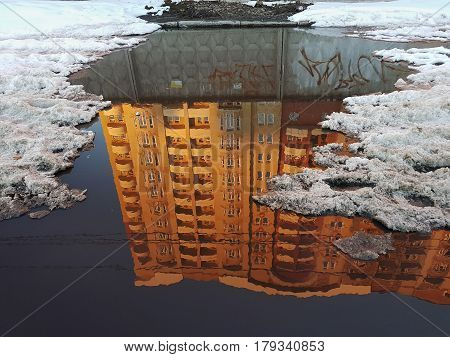 A Puddle, In The Surface Of The Water A Reflection Of A Residential High House, Lit By The Orange Ra