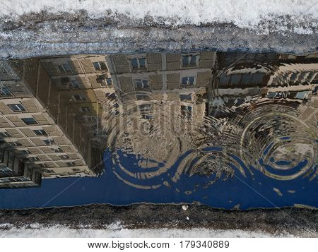 Puddles, From The Rain Drops Circles On The Surface Of The Water, A Mirror Image Of Gray Building Wi