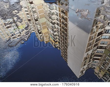 A Large Tall Apartment Building With Many Floors Is Reflected In A Puddle Of Blue Color, Old Snow Li