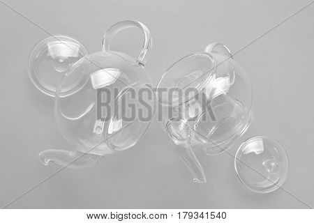 Two Transparent Small Glass Teapot For Tea Lie On A Light Gray Background, Near The Dartboard From T