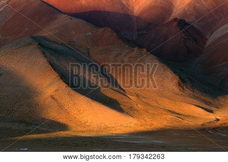 Sunset In The High Mountains: The Huge Brown Slopes Of The Mountains Are Painted With The Sun In An