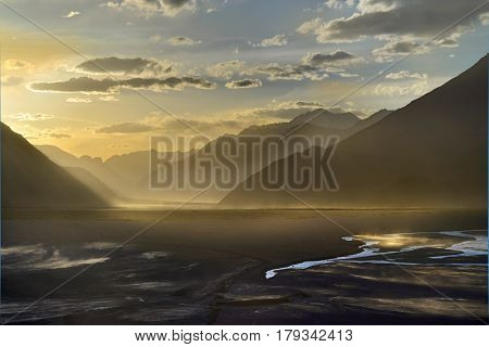 Golden Sunset In The Nubra Valley: Dark Silhouettes Of High Mountains, Golden Ligh, Clouds In The Bl