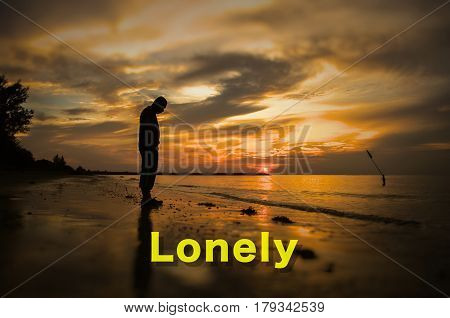 Creative conceptual,Lonely,word on photo with man alone on the beach during sunset.Calm sea with rippling waves.