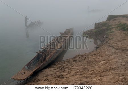 A National Wooden Nepalese Canoe With Inverted Cisterns Stands By The Shore, Other Boats Sail Along