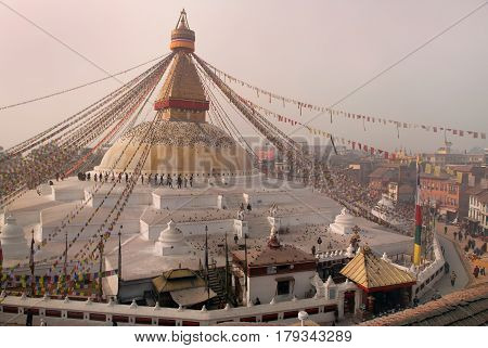 Buddhist Stupa Bodnath: the second largest Buddhist stupa immense white with a gold head of Buddha evening people go and pray a lot of colorful flags Kathmandu Nepal.