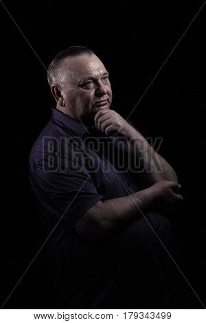 Close up portrait of pensive aged man wearing shirt, looking aside, holding hand under his chin against black background - retirement concept