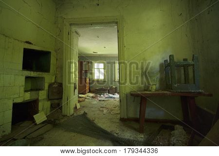 Abandoned Village Private House In Pripyat: Green Walls, Old Russian Stove, On The Wooden Table Ther