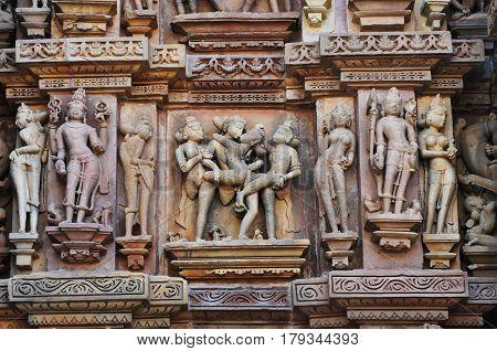 Erotic sculptures illustrating sex in the ancient art system of Kamasutra on walls of Kandariya Mahadeva Temple at Khajuraho in India.