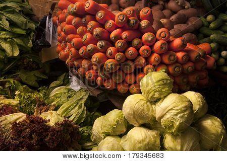 Still life with vegetables on the village market: a slide of green cabbage a basket of bright orange carrots lettuce leaves.