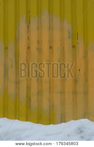Metal Wall Of Yellow Background With Old Dirty Stains Texture With Screws And Bottom Band White Snow