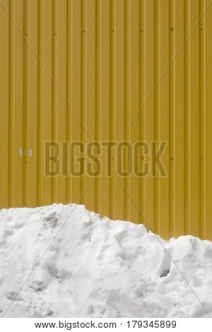 Dark Yellow Striped Metal Wall, The Bottom One-third Of The Frame White Pile Of Old Melting Snow.