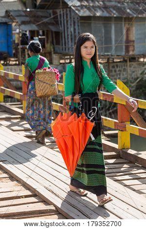 INLE LAKE, MYANMAR - DECEMBER 09, 2016 : woman walking in tradional costume at Inle Lake Shan state in Myanmar