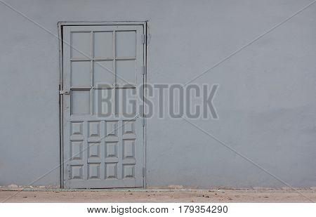 old gray door in concrete wall background