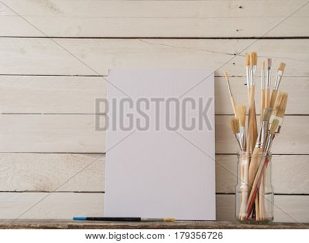 Paint brushes with a canvas on a white barn wood background