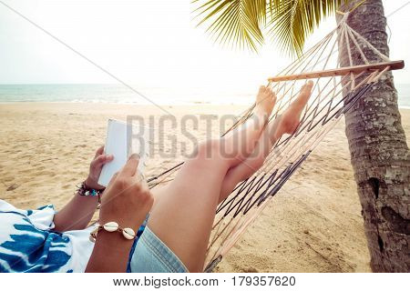 Leisure in summer - Beautiful Tanned of sexy women. relax and reading on hammock at sandy tropical beach. vintage color styles