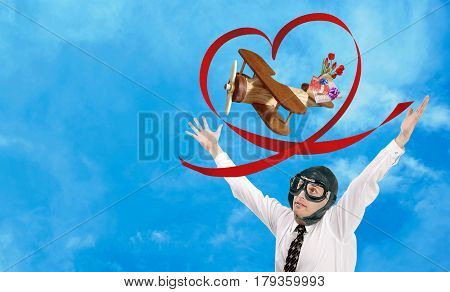 A toy wooden plane flies to congratulate on the holiday beloved. Loving man aviator