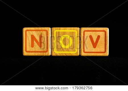 November on wood Cubic on black background
