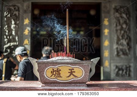 Burning joss sticks outside a Chinese temple in Penang