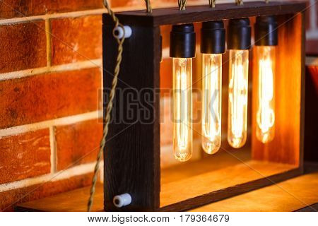Light Bulb Lamp On Dark Red Brick Background With Hotspot Close Up. Loft Horizontal Texture. Grange