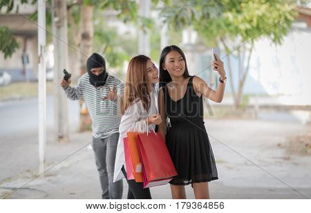 Street thief holding gun and trying to steal and run away the shopping bag and smartphone on footpath from two women holding moblie phone for selfie