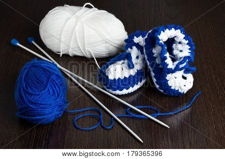 knitted, blue booties for children on a dark background