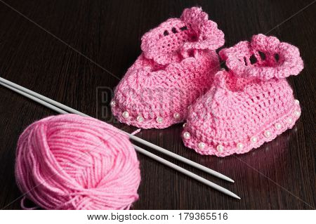knitted, pink booties for children on a dark background