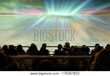 The audience in the brightly lit colored rays hall awaiting the start of the show.