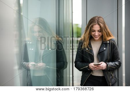 Young modern woman looking to phone outdoor in street standing at shop window