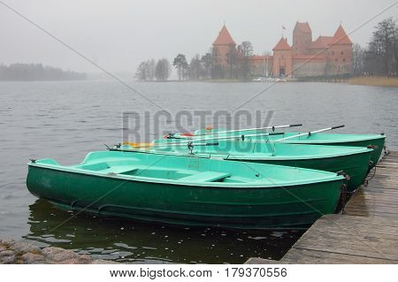 Several green wooden boats on the dock on the lake. Trakai castle in the background in a fog. Lithuania.