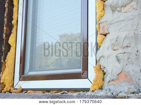 Window installation with mosquito nets. Close up on plastic window insulation with spray foam insulation.