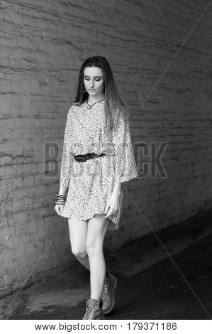 Girl in a short dress and boots walks around the town. Black and white.