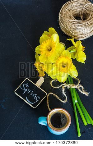 cup of coffee and bright yellow daffodils on dark wooden table