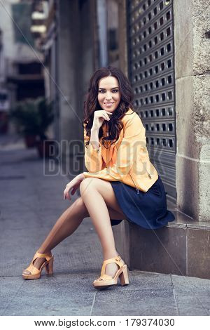 Young Brunette Woman Smiling In Urban Background.