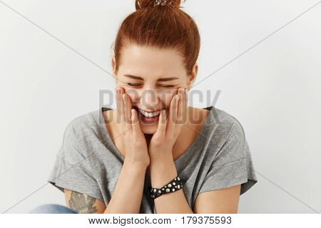 Fashionable Pretty Girl With Hair Knot And Tattoo Dressed In Stylish Grey T-shirt Holding Hands On C