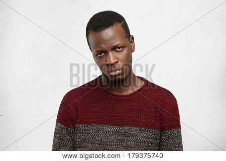 Upset Handsome Young Dark-skinned Male Dressed In Casual Sweater Looking At Camera With Disappointme