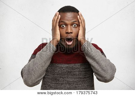 Omg. Forgetful Bewildered Young Afro-american Man Wearing Warm Sweater Keeping Hands On His Head, Sc