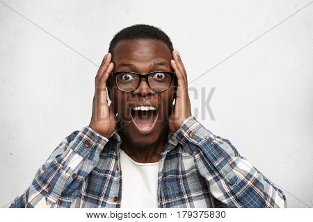 Portrait Of Excited Young African American Male Screaming In Shock And Amazement Holding Hands On He