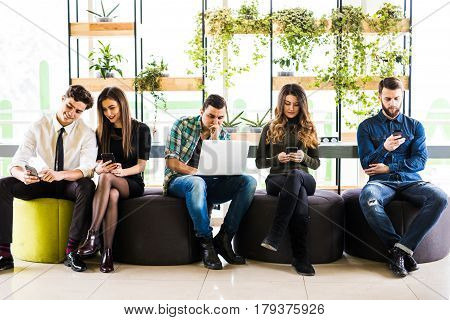 Friends Sitting On Chairs Near Each Other And Everyone Use His Divices In Modern Office Room. Togeth