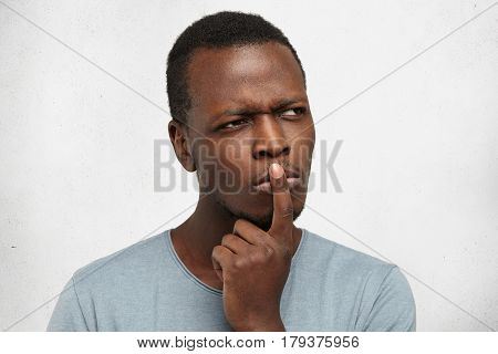 Close Up Studio Portrait Of Handsome Young Black Man Having Concentrated Thoughtful Expression, Frow