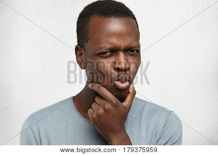 Portrait Of Suspicious Pensive Young Afro-american Male In Casual T-shirt Touching Face While Thinki