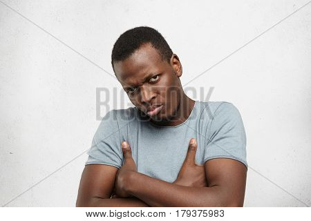 Grumpy And Dissatisfied Young African American Man Wearing Casual Grey T-shirt Frowning, Keeping Arm