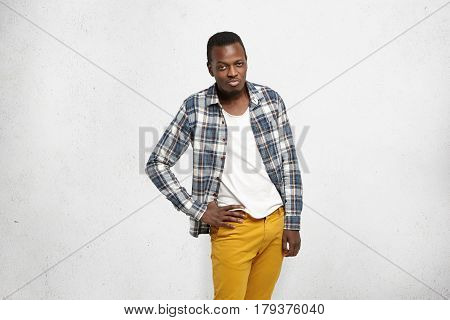 Fashionable Young Afro-american Male Wearing Mustard Denim Pants And Checkered Shirt Over White T-sh