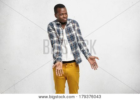 Studio Shot Of Puzzled Dark-skinned Male Student Shrugging Shoulders Having Completely Lost And Conf