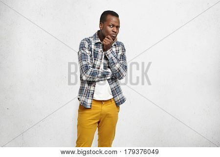 Portrait Of Stylish Young Afro-american Man Dressed In Mustard Jeans And Checkered Shirt Over White