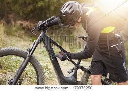 Unrecognizable Caucasian Biker In Helmet And Gloves Pressing Buttons On Frame Of His Black Electric