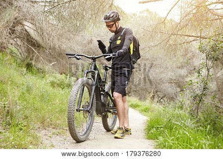 Outdoor Shot Of Caucasian Male Rider Standing On Trail In Forest With His Electric Bike Holding Smar
