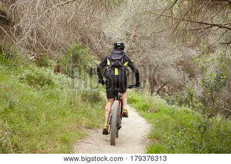 Rear View Of Unrecognizable Young Man Wearing Protective Helmet, Sports Clothes And Backpack Speedin