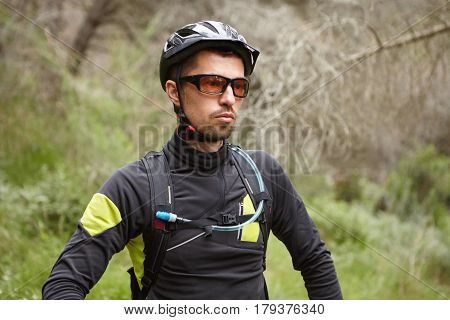 Serious Caucasian Male Cyclist Wearing Protective Helmet And Glasses Feeling Tired After Intensive C