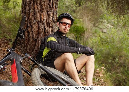 Handsome Young Professional Rider Wearing Glasses And Helmet Sitting Under Tree, Relaxing And Admiri