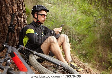 Always In Touch. Confident Male Cyclist Typing Message Or Searching For Gps Coordinates On Smart Pho
